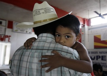 A 3-year-old Texan grips his father, an illegal immigrant, in San Juan
